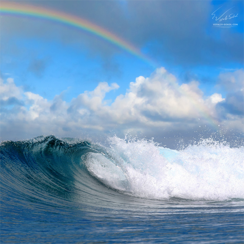 Ocean surfing waves and cloudy sky with rainbow