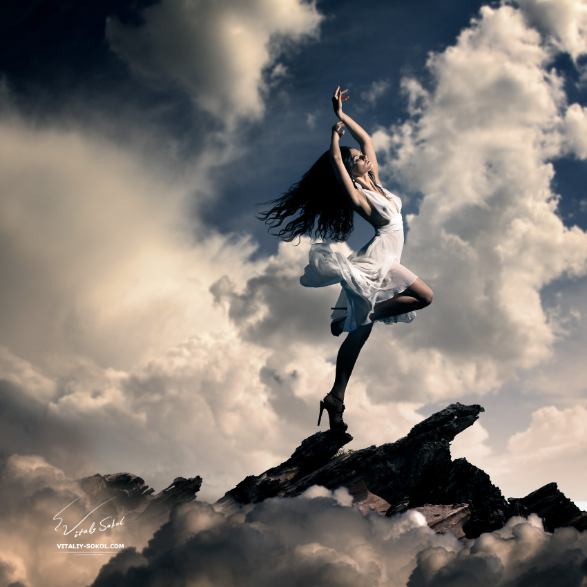 Creative cloudy background. Young girl wearing gorgeous white dress dancing with expression