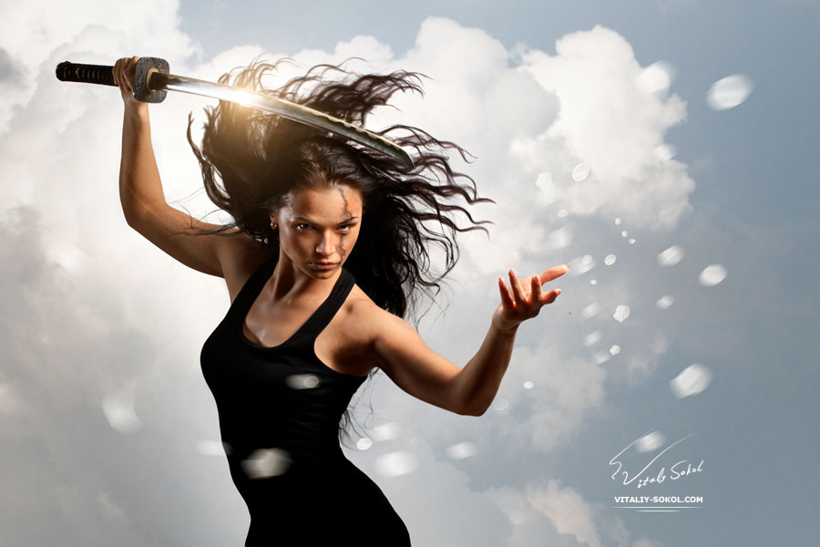 Beautiful Brunette with katana sword in spring floral environment - stock photo