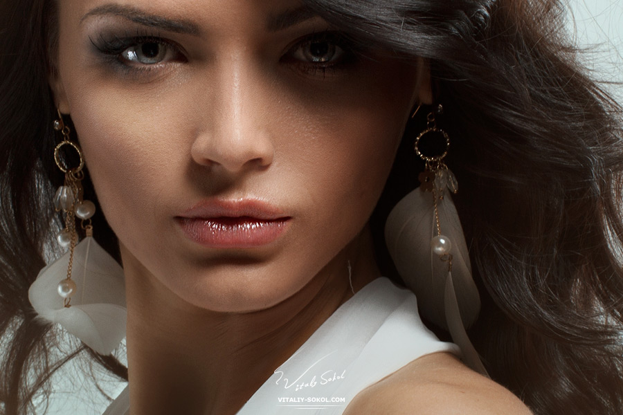 Portrait of beautiful young brunette girl in white dress. Fashion photo