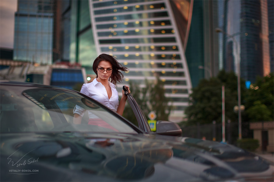 Beautiful brunette going to sit in business car after work. Evening sunset City skyscrapers on background.