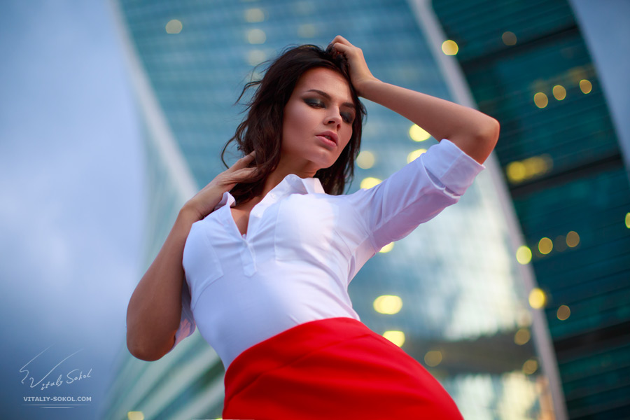 Evening city lights and beautiful brunette in white shirt and red skirt posing. Closeup half body portrait.